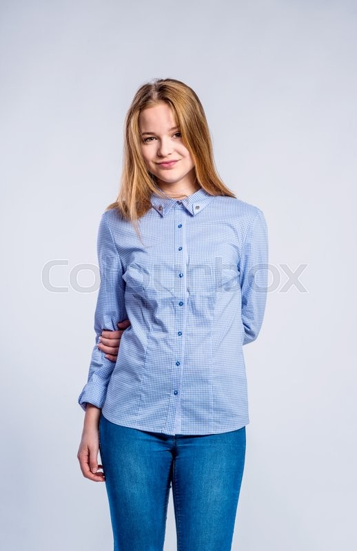 Stock image of 'Teenage girl in jeans and blue checked shirt, young woman, studio shot on gray background'