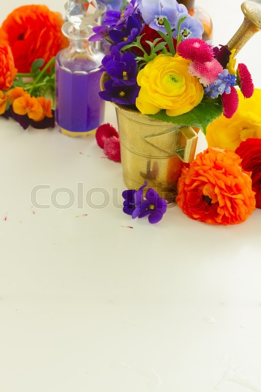 Stock image of 'Fresh flowers, mortar and bottles of potions, herbal medicine concept, copy space on white table'
