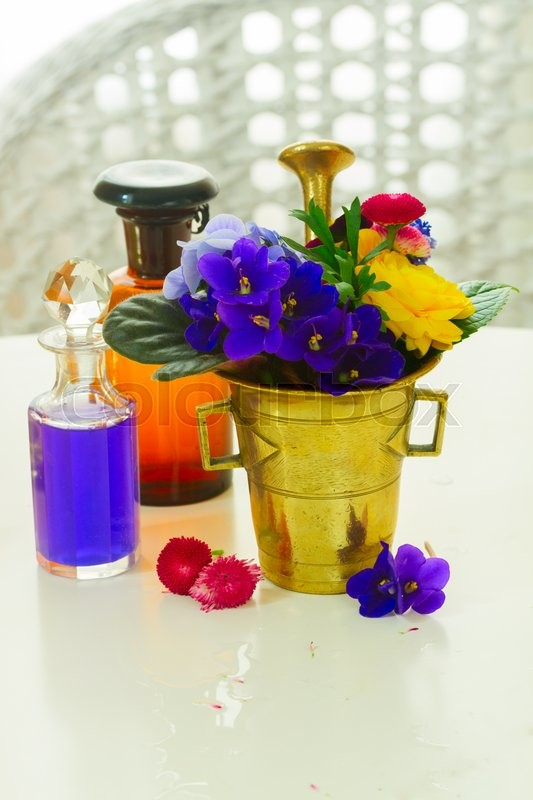 Stock image of 'Flowers, mortar and glass bottles of potions, herbal medicine'