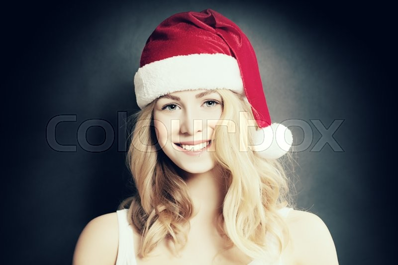 Stock image of 'Christmas Girl. Smiling Woman in Santa Hat on Dark Background'