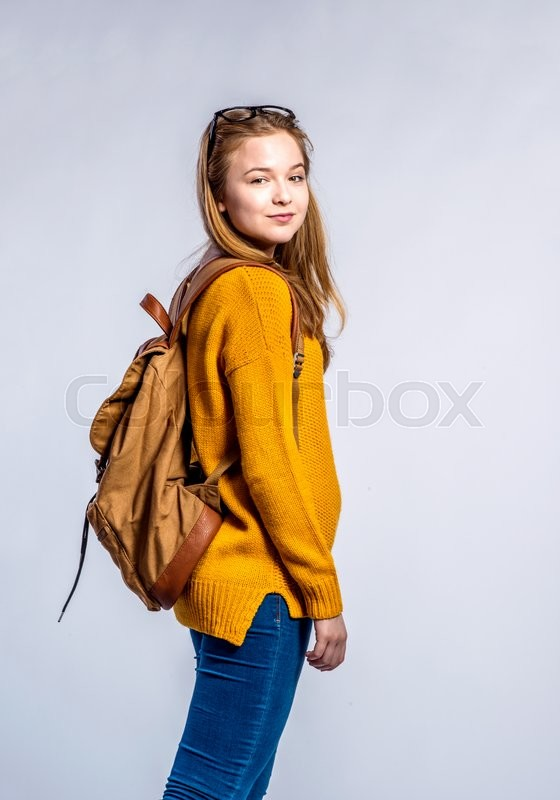 Stock image of 'Teenage girl in jeans, yellow sweater, with backpack on back, young woman, studio shot on gray background'