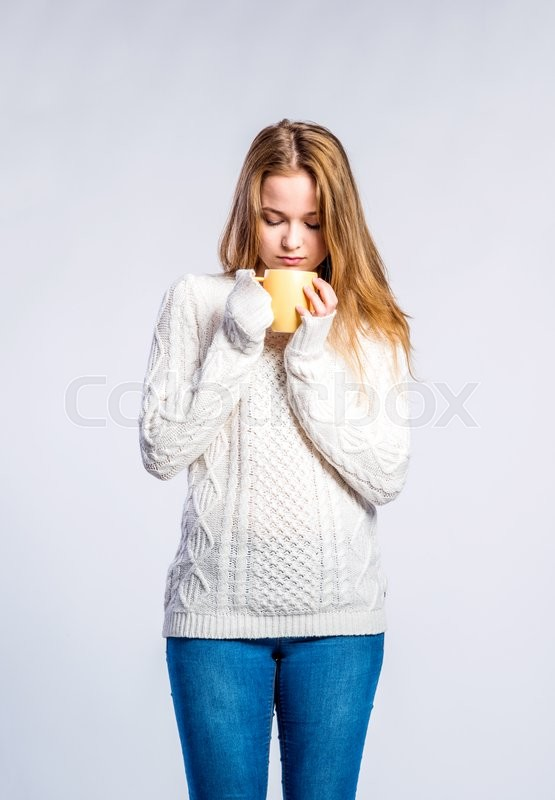 Stock image of 'Teenage girl in jeans and white sweater, holding a cup with hot drink, young woman, studio shot on gray background'