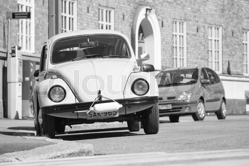 Editorial image of 'Helsinki, Finland - May 7, 2016: Old yellow Volkswagen beetle is parked on a roadside, front view, black and white photo'