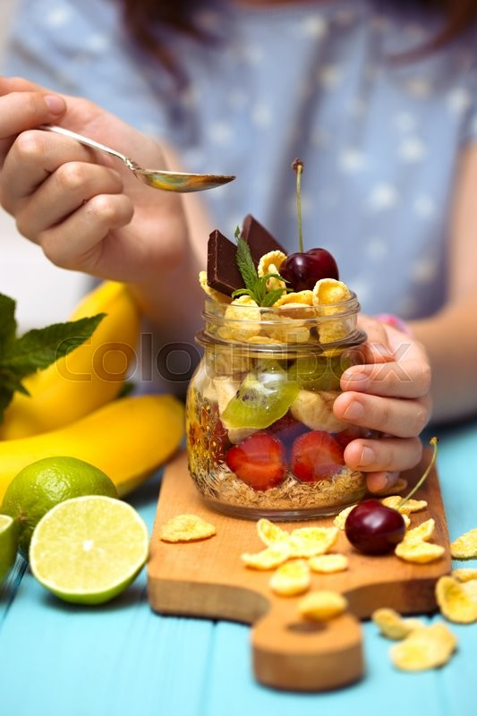 Stock image of 'healthy diet. girl hand with a spoon and oatmeal with berries and fruits\'