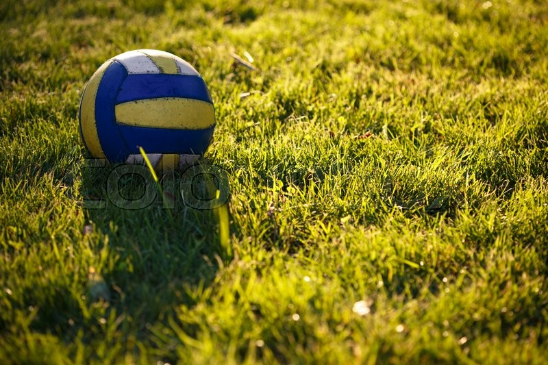 Stock image of 'old soccer ball on a grass at the sunset time\'
