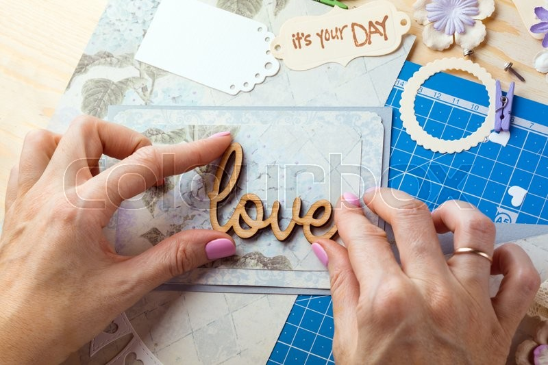 Stock image of 'scrapbook background. Hands, Card and tools with decoration. Love\'