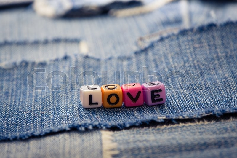 Stock image of 'cubes with letters love on a jeans background\'