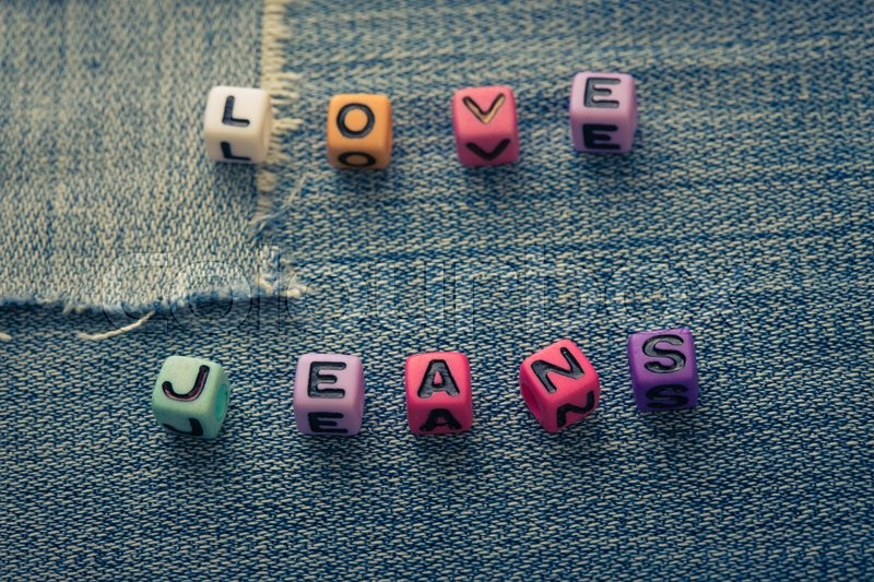 Stock image of 'cubes with letters love jeans on a jeans background\'