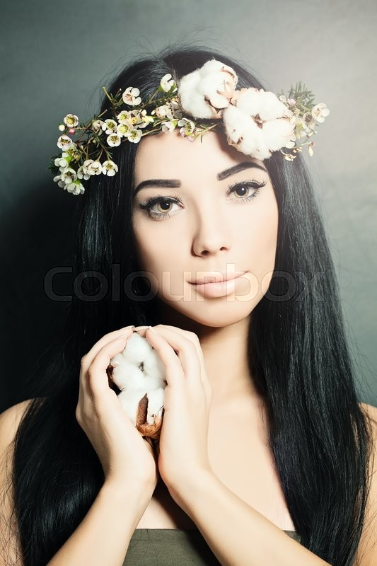 Stock image of 'Beautiful brunette woman with cotton flowers in her hair and hand. Fashion photo'