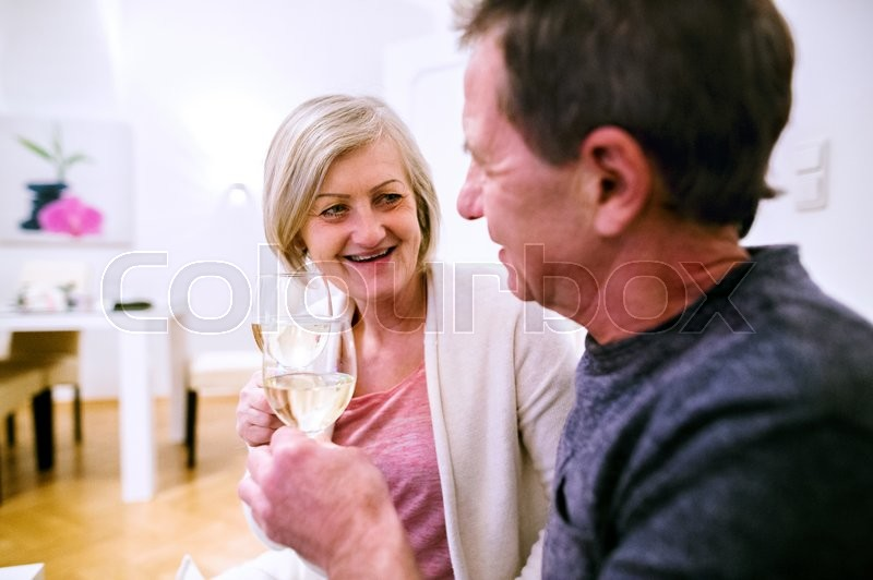 Stock image of 'Senior woman and man sitting in living room on sofa, drinking champagne'