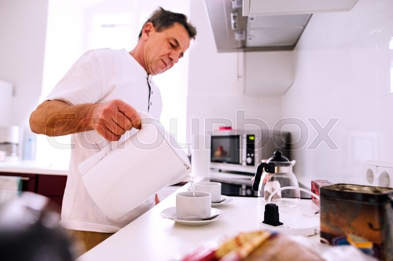 Stock image of 'Senior man preparing coffee. Pouring hot water from electric kettle into prepared cups.'