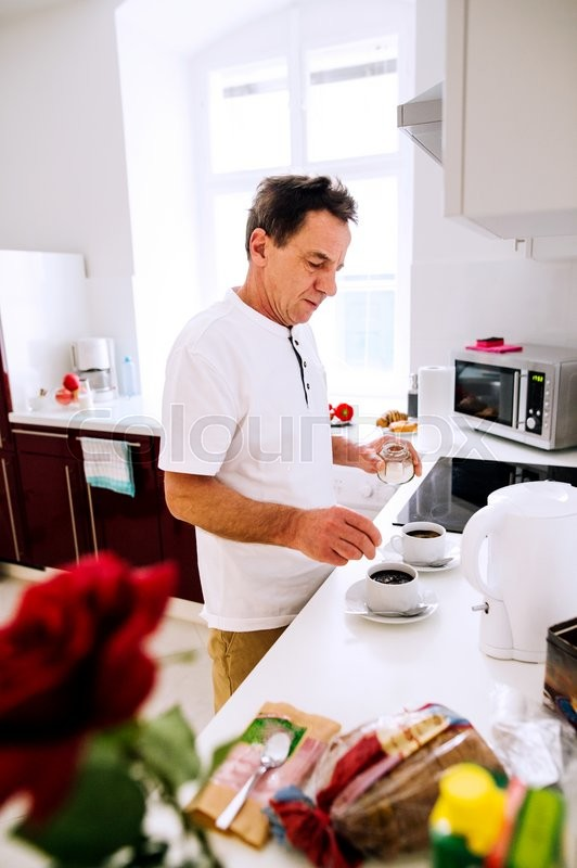 Stock image of 'Senior man preparing coffee. Putting sugar in two white cups.'