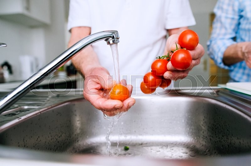 Stock image of 'Hands of unrecognizable senior man in white t-shirt washing tomatoes under the tap. Preparing breakfast.'