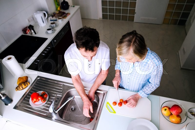 Stock image of 'Senior man and woman preparing breakfast. Sunny morning. Domestic kitchen.'