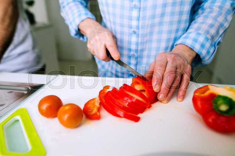 Stock image of 'Hands of unrecognizable senior woman in checked blue shirt cutting red peppers. Preparing breakfast.'