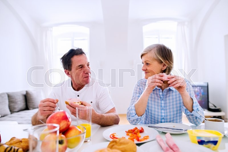 Stock image of 'Senior man and woman having breakfast. Sunny morning. Table with food.'