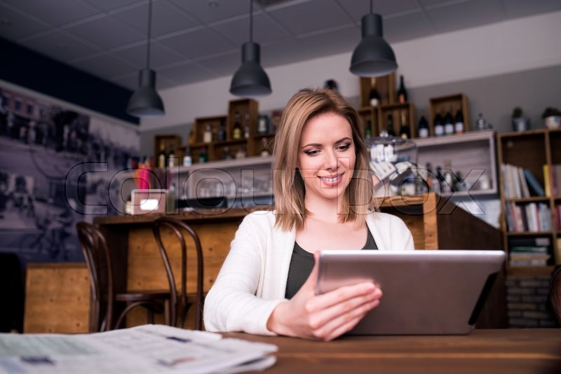 Stock image of 'Blond woman with tablet in cafe sitting at the table, reading'