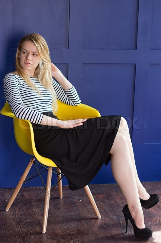 Stock image of 'Blond girl in a long skirt and a vest sits on a chair next to the blue walls'