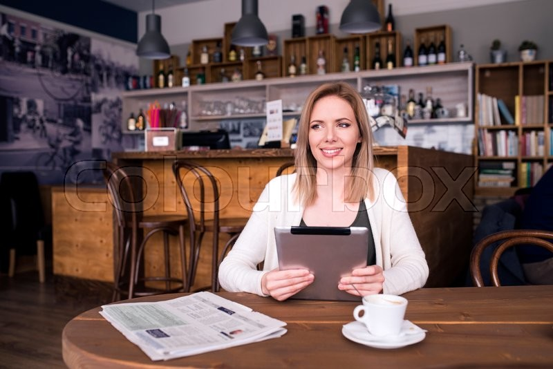 Stock image of 'Blond woman with tablet in cafe sitting at the table drinking coffee'