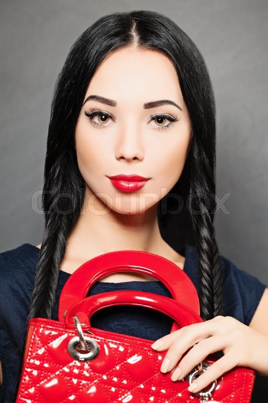 Stock image of 'Portrait of a beautiful brunette woman with red handbag in her hand. Fashion photo'