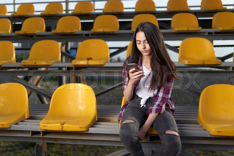 Stock image of 'girl sitting in the stands and looks at a mobile phone'