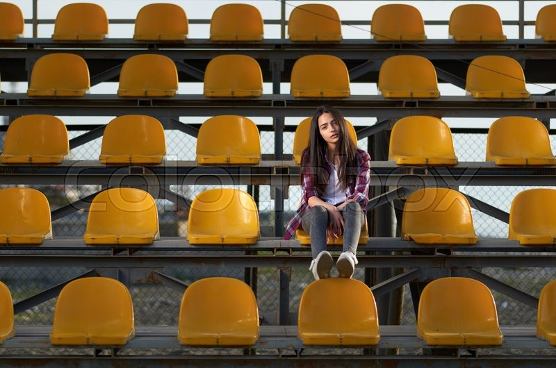 Stock image of 'lonely teen girl sitting on tribunes, front view'