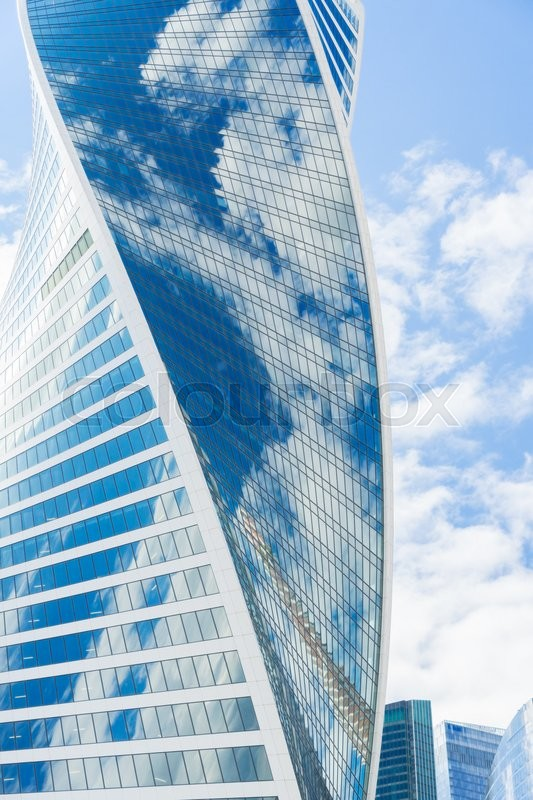Stock image of 'modern skyscrapers of steel and glass reflecting blue sky and clouds'