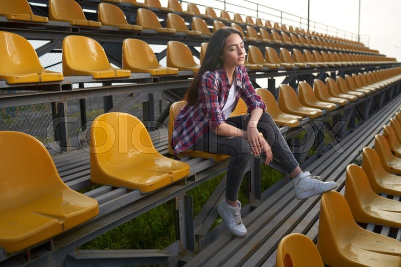 Stock image of 'beautiful lonely woman sitting on tribunes and looks aside. Side view.'