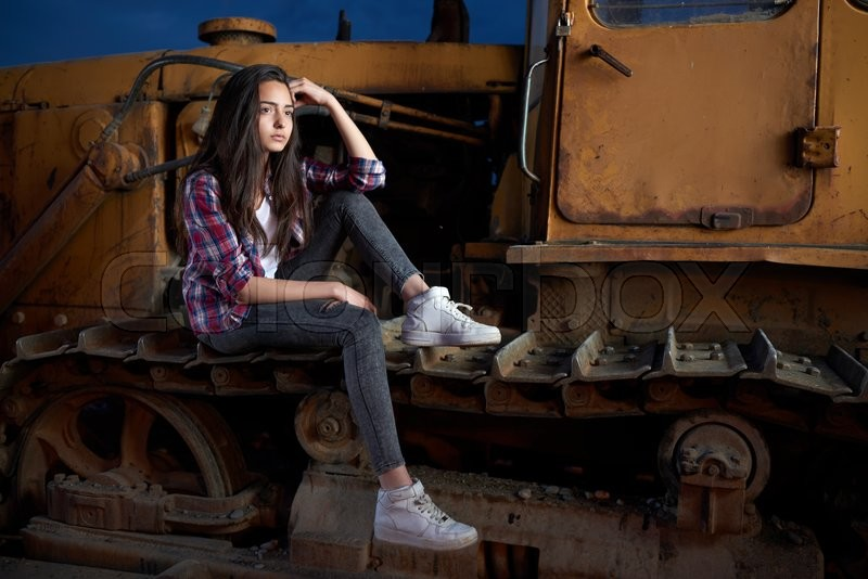 Stock image of 'beautiful teen girl sitting on an old tractor tracks.'