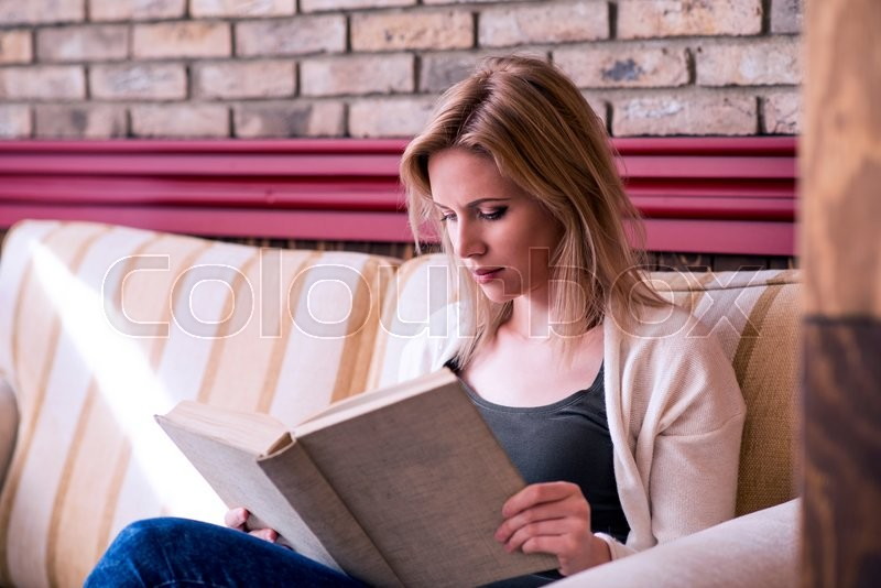 Stock image of 'Blond woman with newspaper in cafe sitting at the table drinking coffee'