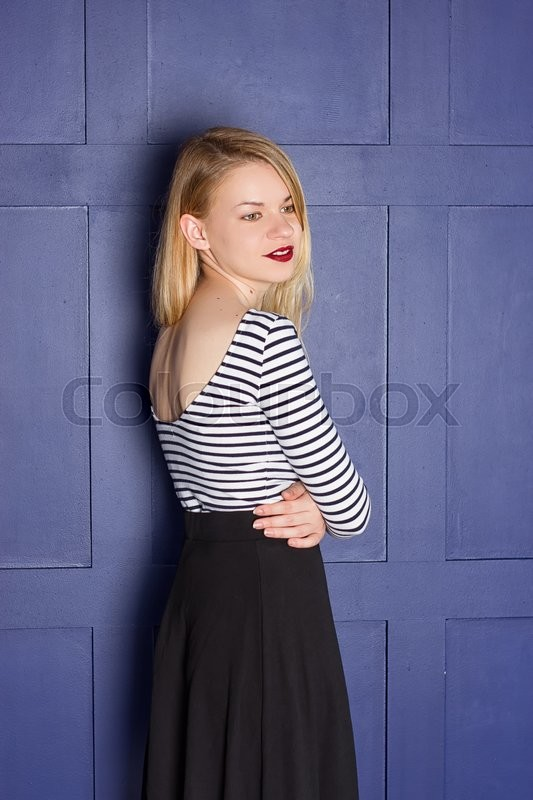 Stock image of 'Beautiful blonde in a shirt-vest near a blue wall'