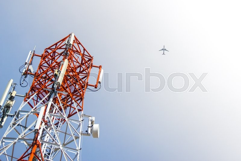 Stock image of 'Mobile phone communication antenna tower and airplane'