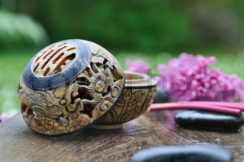 Stock image of 'incense burner and stick with lilacs and pebble on a plank in garden '