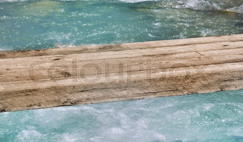Stock image of 'wooden gateway crossing white water '