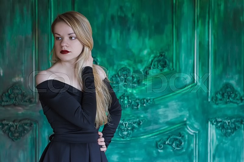 Stock image of 'Elegant blonde in a black dress near grunge wall green'