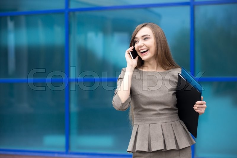 Stock image of 'Portrait of cheerful young woman talking on smartphone and laughing outdoors. Happy beautiful caucasian woman using mobile phone, making call on the street in summer. Copy space'