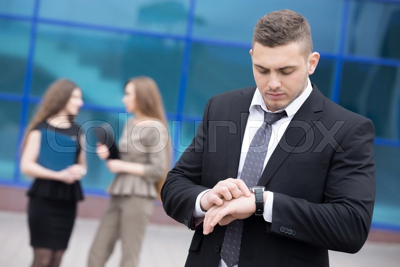 Stock image of 'Portrait of confident young business man looking at watch with serious facial expression outdoors. Successful attractive  caucasian man on the street in summer with businesspeople on the background'