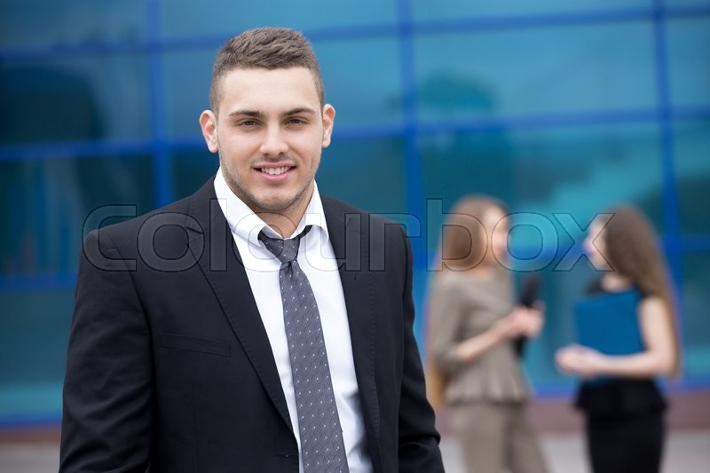 Stock image of 'Portrait of confident young business man looking at camera with happy facial expression outdoors. Successful attractive  caucasian man posing on the street with businesspeople on the background'