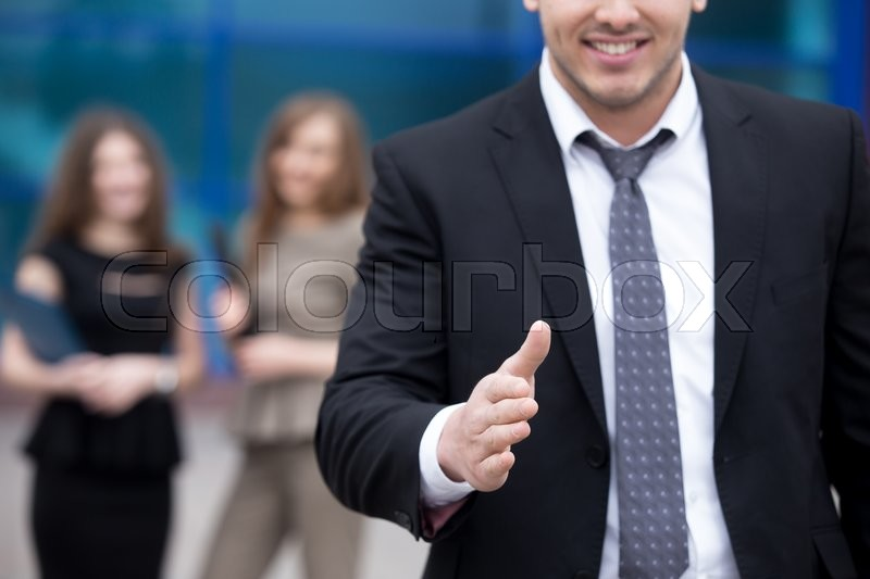 Stock image of 'Confident young business man offering hand for greeting or agreement handshake outdoor. Successful Deal Concept. Businesspeople Team on the background. Close-up'