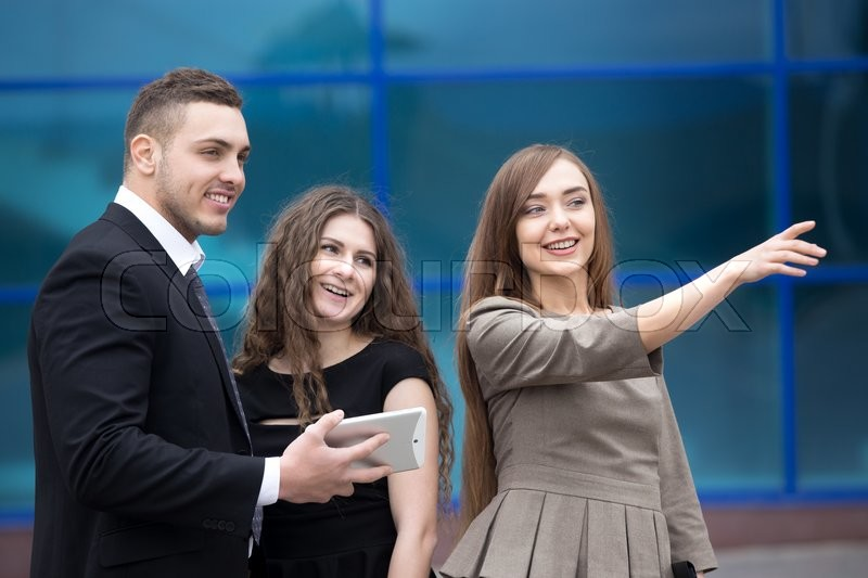 Stock image of 'Portrait of beautiful business woman meeting with clients or partners outdoors. Successful attractive caucasian real-estate agent showing property to happy laughing young couple'