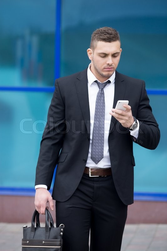 Stock image of 'Portrait of serious young business man looking at smartphone screen while walking outdoors. Handsome caucasian man using mobile phone app, making call or messaging on the street in summer'