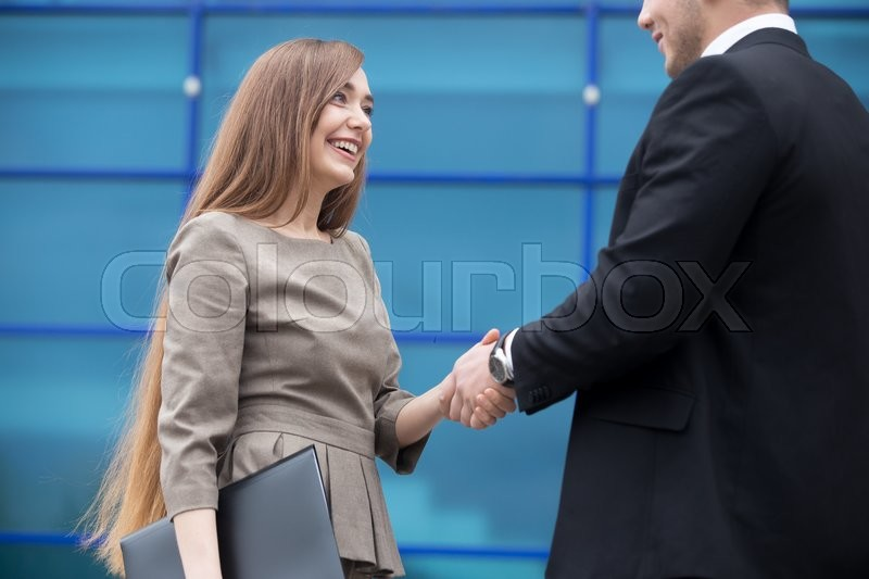 Stock image of 'Successful business people shaking hands for greeting or in agreement happy to work together. Focus on smiling businesswoman. Successful Deal Concept. Businesspeople Teamwork'