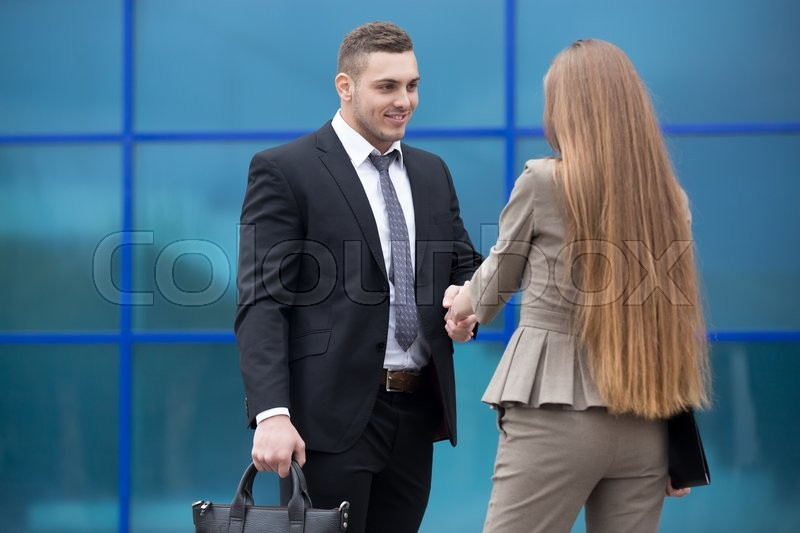 Stock image of 'Successful business people shaking hands for greeting or in agreement happy to work together. Focus on smiling businessman. Successful Deal Concept. Businesspeople Teamwork'