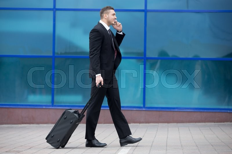 Stock image of 'Profile view portrait of cheerful young man on business trip walking with his luggage while talking on smartphone in front of modern glass building outdoors. Travelling guy making call. Copy space'