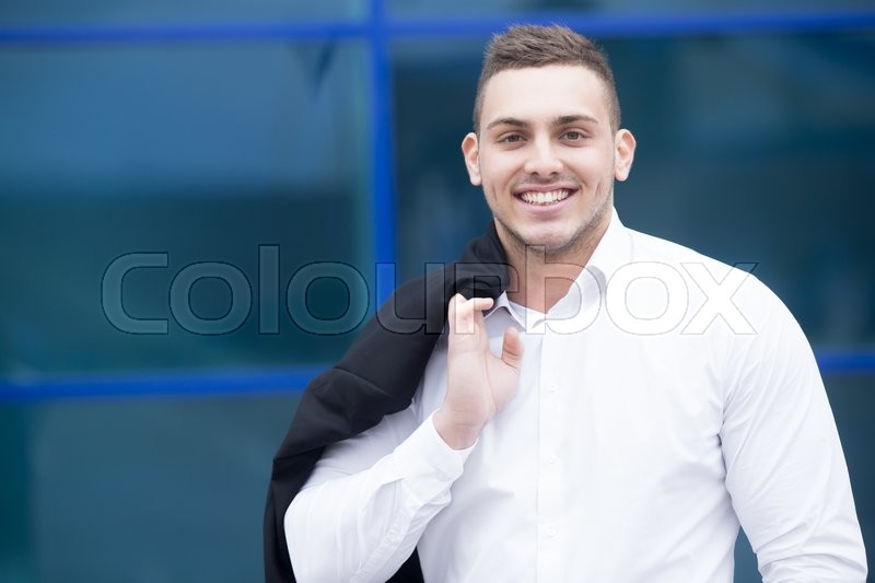 Stock image of 'Portrait of confident young business man looking at camera with happy facial expression outdoors. Successful attractive caucasian man posing on the street and smiling'
