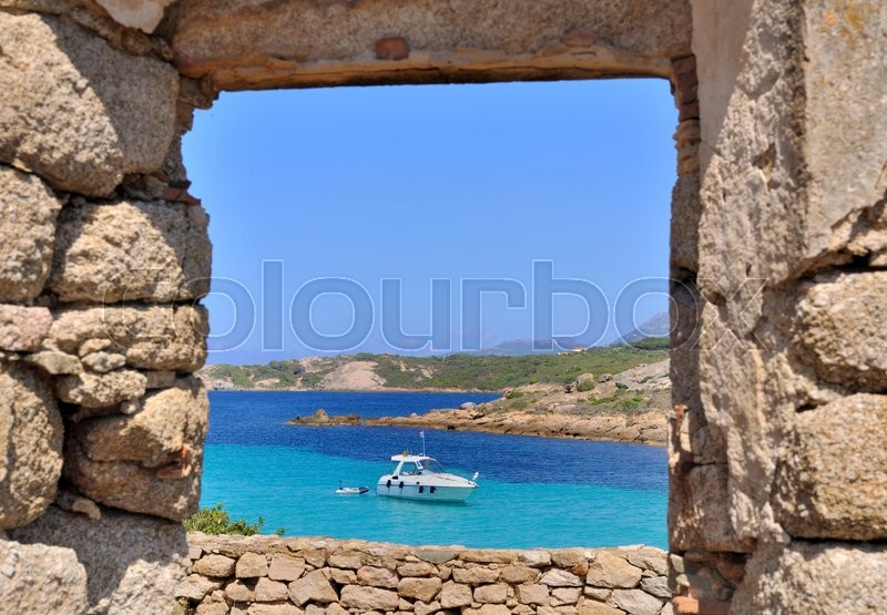 Stock image of 'overlooking the turquoise blue sea through a window of a old stone building'
