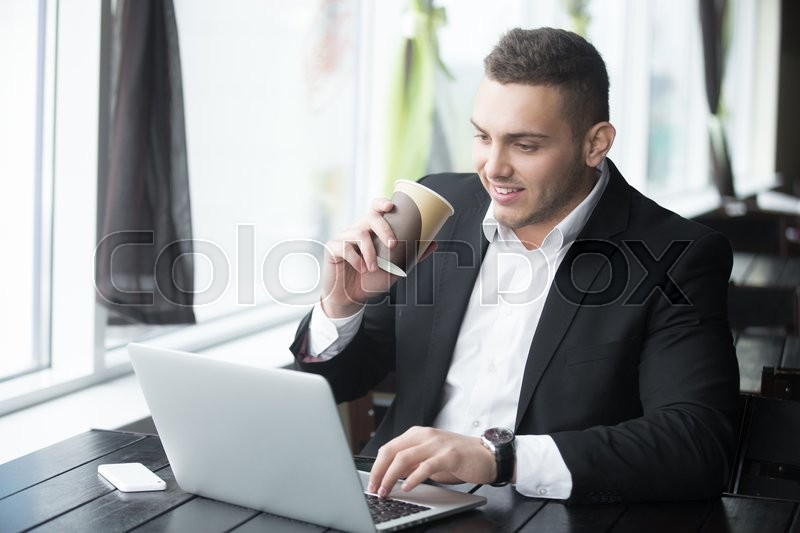 Stock image of 'Portrait of confident happy smiling young business man sitting with glass of drink in coffee shop interior. Successful attractive caucasian man using notebook computer, typing in cafe. Indoors'