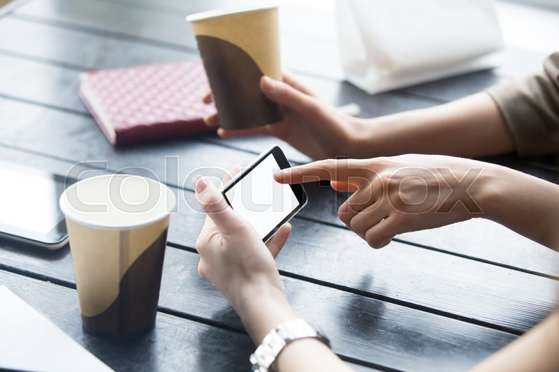 Stock image of 'Two beautiful young girlfriends using app on smartphone in modern coffee shop interior. Close-up of hands and empty phone display. Woman touching mobile phone screen with blank white copy space'