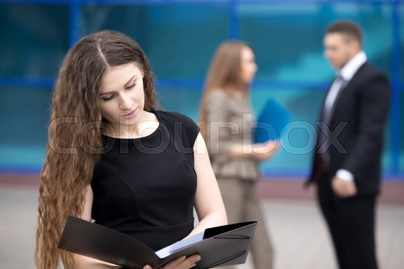 Stock image of 'Portrait of confident young woman looking through documents with serious facial expression outdoors. Successful beautiful woman posing on the street in summer with businesspeople on the background'