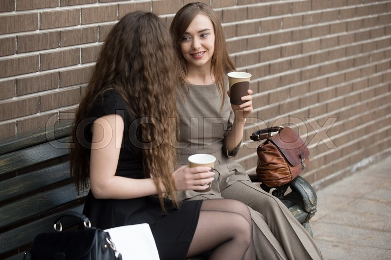 Stock image of 'Portrait of two beautiful young girlfriends sitting on bench outdoors and talking with happy smiles. Successful attractive women friends holding paper cups of coffee and chatting during break time'